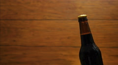 Cold bottle of beer on wood broun background. Drop flows down the bottle Stock Footage