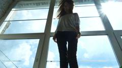 Young pretty girl dancing on windowsill Stock Footage