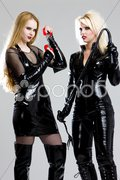 Women in latex with handcuffs and whip Stock Photos