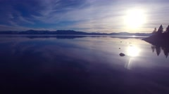 A beautiful aerial shot over Lake Tahoe with the shoreline in silhouette. Stock Footage