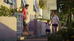 Young children returning home from school Stock Footage