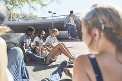 Teenage friends hanging out skateboarding at sunny skate park Stock Photos