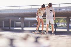 Teenage boy teaching girlfriend skateboarding at sunny skate park Stock Photos