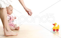 Baby girl with a toy sitting on the floor Stock Photos
