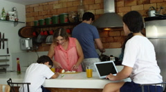 Mother and father cooking and preparing dinner while children do homework Stock Footage