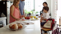 Family eating breakfast early in the morning before school Stock Footage