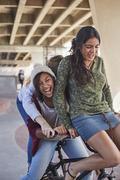 Playful teenage girls riding BMX bicycle at skate park Stock Photos