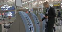 Woman using self-service machine to check-in Stock Footage