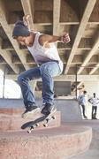 Teenage boy jumping skateboard at skate park Stock Photos