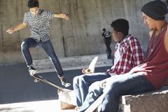 Friends watching teenage boy doing stunt at skate park Stock Photos