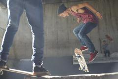 Teenage boy flipping skateboard at skate park Stock Photos