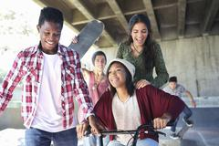 Teenage friends with skateboards and BMX bicycle at skate park Stock Photos