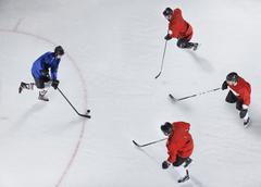 Hockey defenders guarding opponent with puck on ice Stock Photos