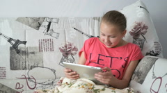 Little girl lying on the bed with a digital tablet Stock Footage