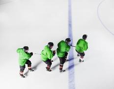 Hockey team in green uniforms skating in a row on ice Stock Photos