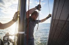 Man adjusting sailing rigging on sailboat Stock Photos