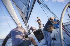 Men sailing adjusting rigging and sail on sailboat Stock Photos