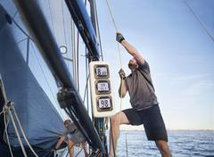 Man adjusting sailing equipment on sailboat Stock Photos