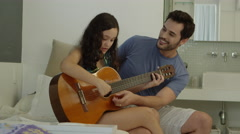 Father teaching young daughter play the guitar Stock Footage