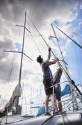 Men adjusting sailing equipment on sailboat Stock Photos