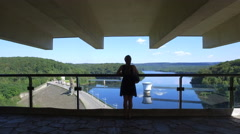 Caucasian female looking over the Gileppe lake and dam, Belgium Stock Footage