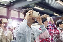 Audience trying virtual reality simulator glasses at technology conference Stock Photos