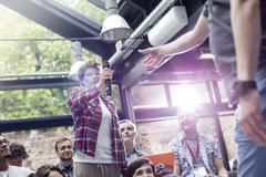 Woman in audience handing speaker microphone at conference Stock Photos