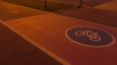 Two bicycles passing by on urban bike path at night. 4K shot Stock Footage