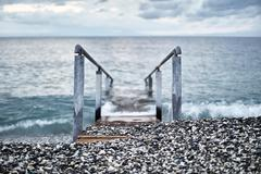 Ramp with railing leading into ocean, Devon, United Kingdom Stock Photos