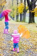 Mother and her daughter with umbrellas in autumnal alley Stock Photos