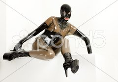 Sitting woman wearing latex clothes Stock Photos