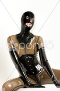 Portrait of sitting woman wearing latex clothes Stock Photos