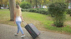 Girl with a suitcase walking along the park. Stock Footage