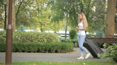 Woman walking with luggage in hands, talking on smartphone Stock Footage