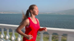 Young Fitness Woman Having An Exercise Run at sea coastline in the sunny morning Stock Footage