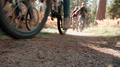 Four friends riding past on bikes in a forest, low angle Stock Footage