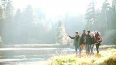 A group of friends hiking near lake stop to admire the view Stock Footage