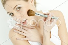 Portrait of young woman putting on face powder Stock Photos