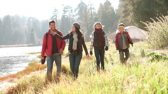 Parents with kids walking near lake admire the view and wave Stock Footage