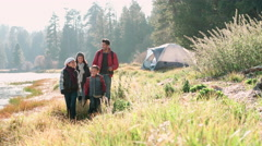 Parents on a camping trip with two kids walking near a lake Stock Footage