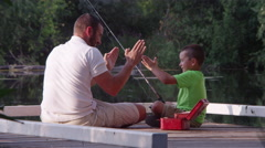 Father and son sitting on dock with fishing pole Stock Footage