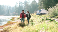 Couple holding hands walking near lake on a camping trip Stock Footage