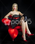 Young woman wearing black dress sitting in armchair Stock Photos