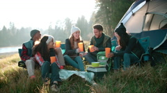 Group of friends on a camping trip sitting outside a tent Stock Footage