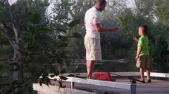 Father and son skipping stones and fishing Stock Footage