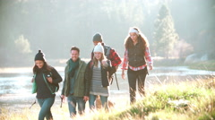 Five friends on a camping trip walking in a row near a lake Stock Footage
