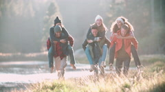Six friends have fun piggybacking in the countryside by lake Stock Footage