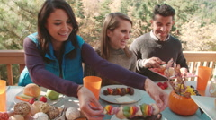 Friends passing food around the table at barbecue, handheld Stock Footage