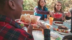 Over shoulder view of friends eating at a table outdoors Stock Footage