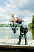Fishing woman with landing net standing on pier Stock Photos